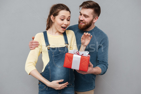 Happy cheerful husband giving present box to his pregnant wife Stock photo © deandrobot