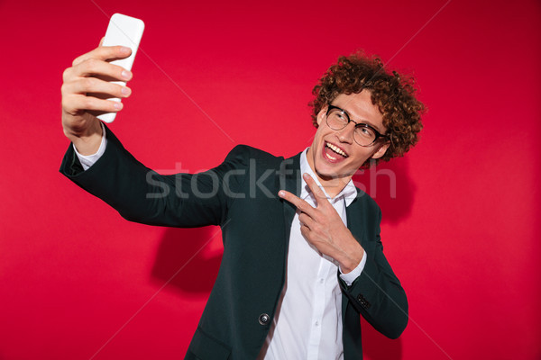 Happy man in eyewear taking selfie and showing peace gesture Stock photo © deandrobot