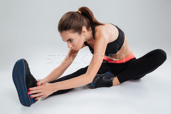 Concentrated fitness woman sitting on the floor Stock photo © deandrobot