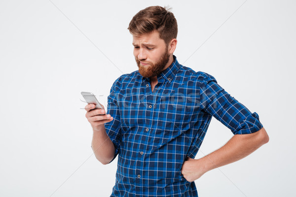 Upset bearded man in checkered shirt using smartphone Stock photo © deandrobot