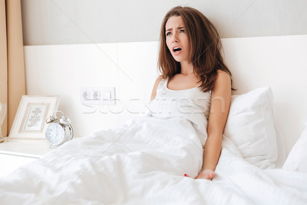Tired upset woman laying in bed Stock photo © deandrobot