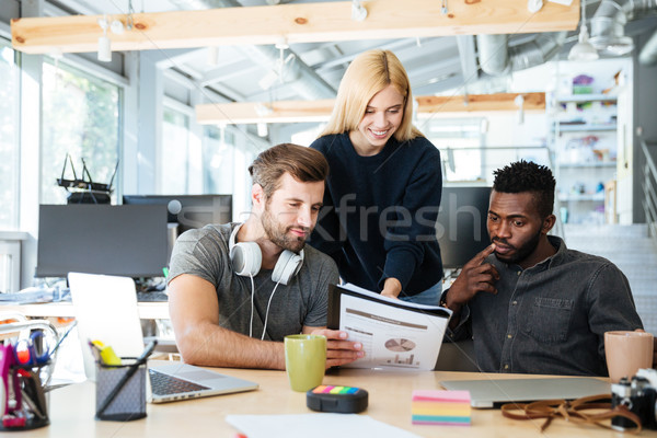 Young happy colleagues sitting in office coworking. Stock photo © deandrobot