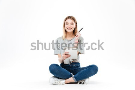 Young woman using pencil and notebook Stock photo © deandrobot
