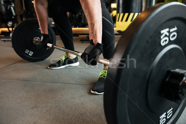 Cropped image of a sportsman holding heavy barbell Stock photo © deandrobot