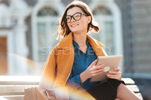Happy woman in eyeglasses holding tablet computer and looking away Stock photo © deandrobot