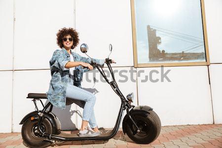 Stylish young woman sitting on a modern motorbike Stock photo © deandrobot