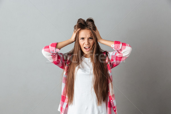 Stressed young woman in rage touching head and screaming with op Stock photo © deandrobot