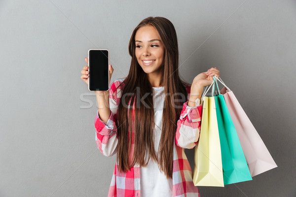 Photo of pretty woman holding shopping bags, showing blank mobil Stock photo © deandrobot