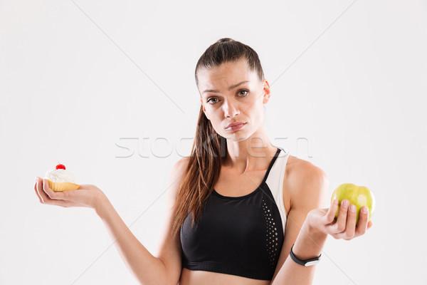 Young doubting sportswoman choosing Stock photo © deandrobot