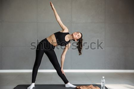 Portrait of a healthy fit sportswoman holding balance during exercise Stock photo © deandrobot