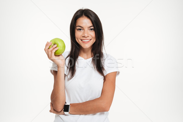 Portrait of a happy fit woman holding green apple Stock photo © deandrobot