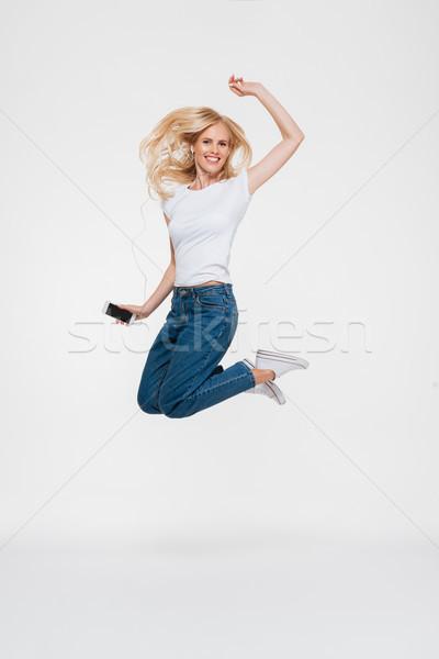 Teljes alakos portré mosolyog szőke nő fülhallgató lezser Stock fotó © deandrobot
