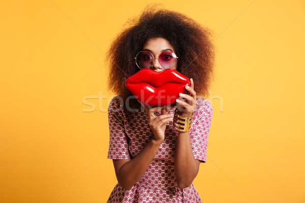 Close-up portrait of playful african wooman in sunglasses holdin Stock photo © deandrobot