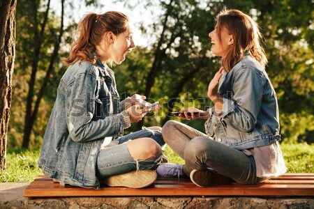 Two smiling young woman in jeans jacket using mobile phone, sitt Stock photo © deandrobot