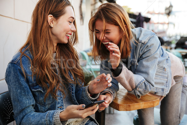 Two young pretty girls in casual stylish wear laughing while sit Stock photo © deandrobot