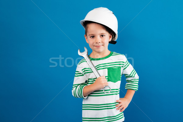 Cheerful young boy in protective helmet posing with wrench Stock photo © deandrobot