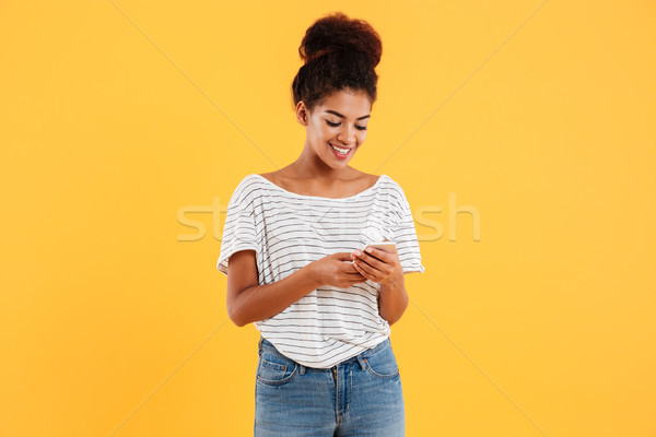 Cheerful african lady using and typing smartphone isolated Stock photo © deandrobot