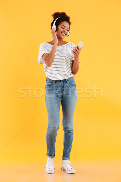 Full length image of happy african woman listening music Stock photo © deandrobot