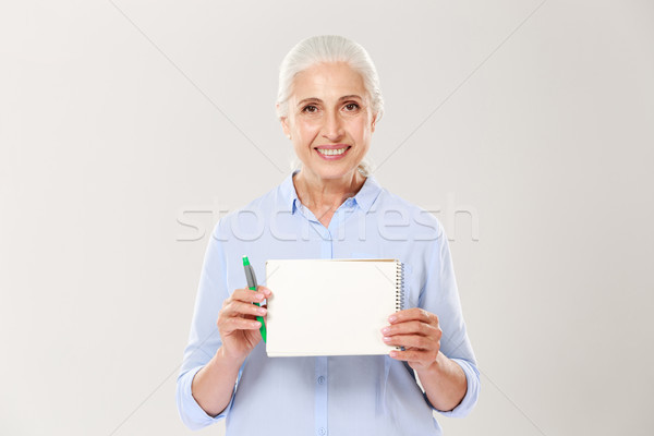 Smiling mature woman showing notebook with copy space for text isolated Stock photo © deandrobot