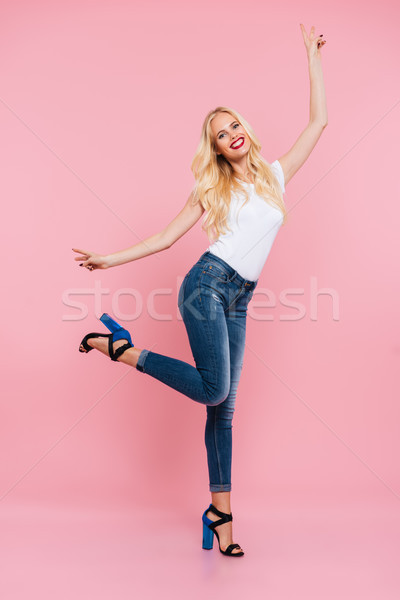 Full-length image of happy carefree blonde woman posing in studio Stock photo © deandrobot