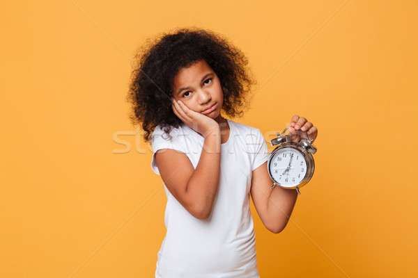 Portrait of a tired little african girl holding alarm clock Stock photo © deandrobot