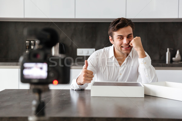 Smiling young man filming his video blog episode Stock photo © deandrobot