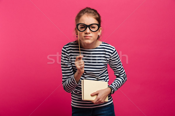 Concentrated teenage girl holding book and fake glasses Stock photo © deandrobot