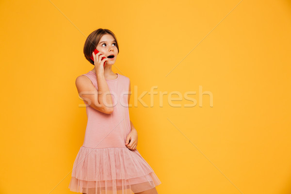 Thoughtful girl looking up at copy space and talking on smartphone isolated Stock photo © deandrobot