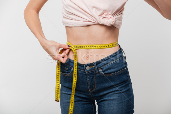 Close up of a slim woman holding measuring tape Stock photo © deandrobot