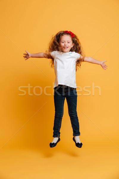 Cheerful little girl child jumping Stock photo © deandrobot