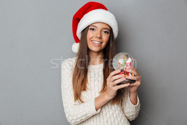 Happy brunette woman in sweater and christmas hat holding toy Stock photo © deandrobot