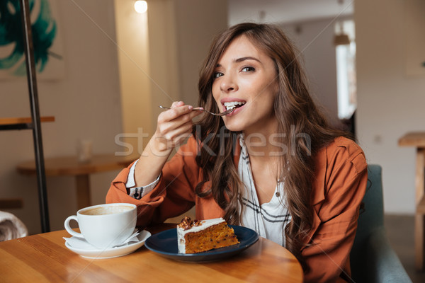 Portrait of a happy woman eating a piece of cake Stock photo © deandrobot
