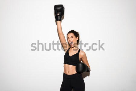 Screaming brunette fitness woman in boxing gloves with hand overhead Stock photo © deandrobot