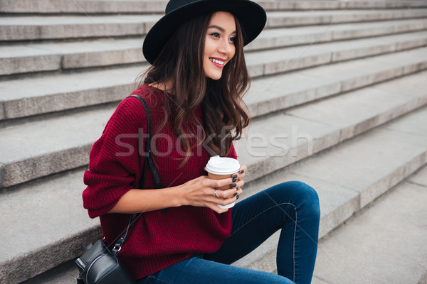 Side view of pleased brunette woman in hat and sweater Stock photo © deandrobot