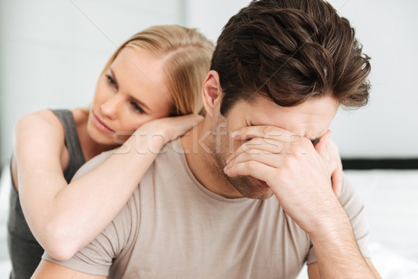 Pensive unhappy woman comfort her sad man while they sitting in bed Stock photo © deandrobot