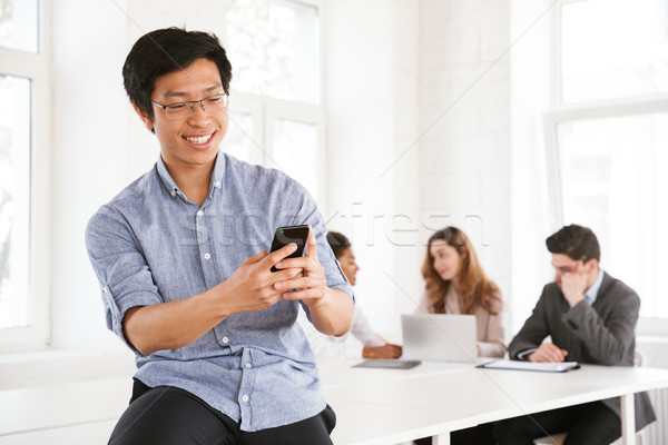 Stock photo: Happy young asian man using mobile phone