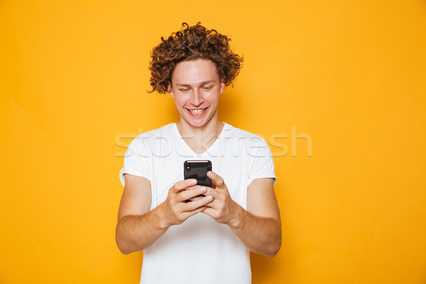 Brunette curly man in casual white t-shirt holding and using mob Stock photo © deandrobot
