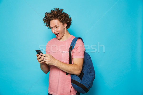 Photo of handsome college guy with curly hair wearing casual clo Stock photo © deandrobot