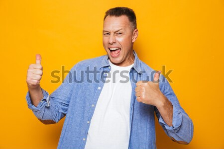 Portrait of a happy middle aged man pointing finger Stock photo © deandrobot
