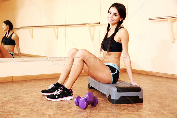 Young happy fit woman sitting on the step board at gym Stock photo © deandrobot