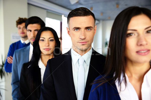 Group of a serious business people standing in a row in office Stock photo © deandrobot