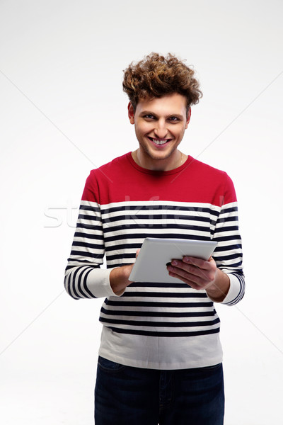 Cheerful casual man using tablet computer over gray background Stock photo © deandrobot