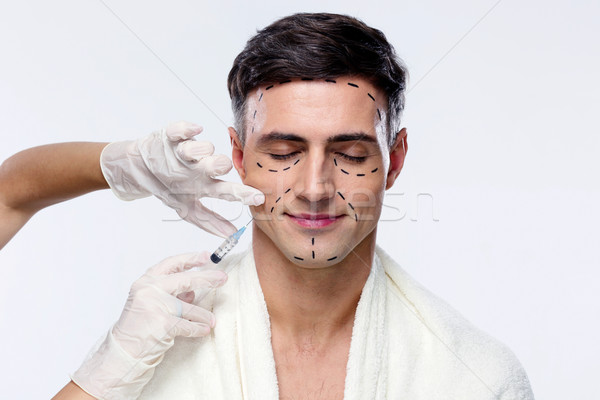 Man with closed eyes at plastic surgery with syringe in his face Stock photo © deandrobot