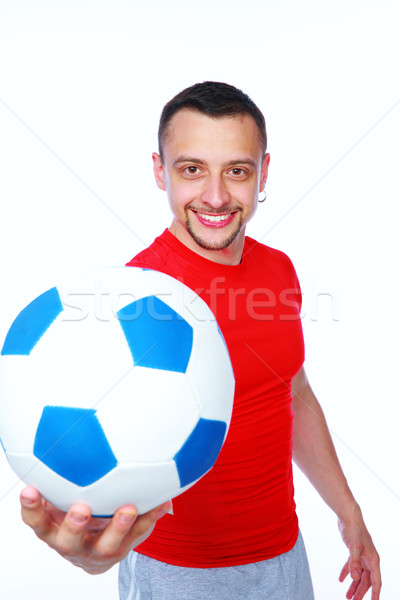 Happy sportive man holding soccer ball over white background Stock photo © deandrobot