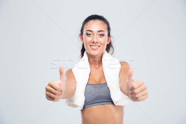 Fitness woman with towel showing thumbs up Stock photo © deandrobot
