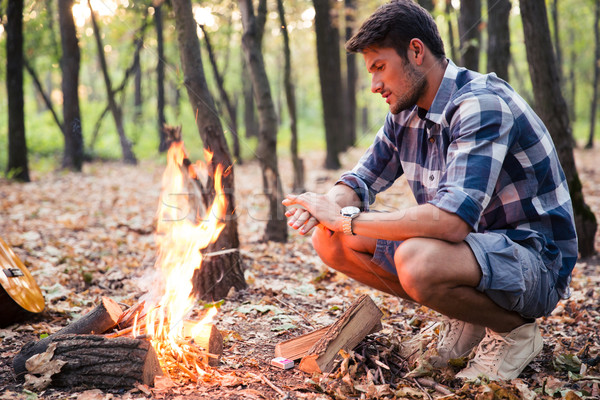 Stock photo: Man sitting near bonfire in the forest