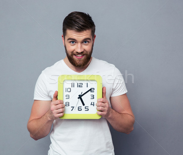 Portrait of a happy man holding wall clock  Stock photo © deandrobot