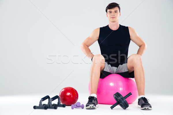 Portrait of a fitness man sitting on the ball  Stock photo © deandrobot