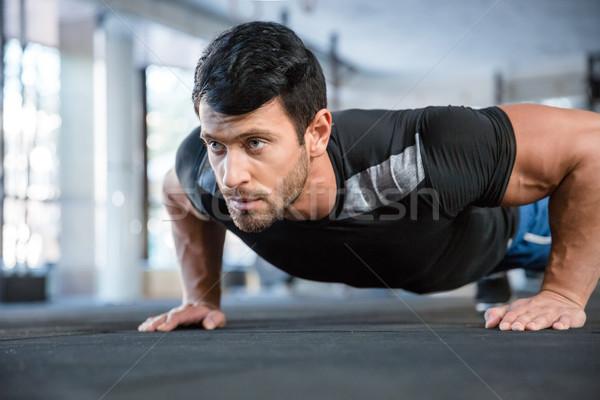 Man doing push ups in gym Stock photo © deandrobot