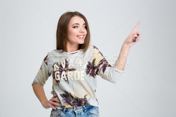 Mujer sonriente tocar invisible Screen sonriendo casual Foto stock © deandrobot